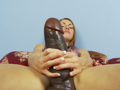 A sexy thing is pushing a large dildo into her meaty and sexy cunt
