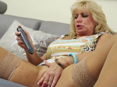 A granny plays with her aged pink slit with a dildo close up