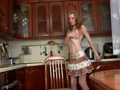 A blonde is in the kitchen, sitting down on a sizeable rubber dildo