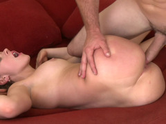 A sexy chick is getting her pussy penetrated on the red sofa