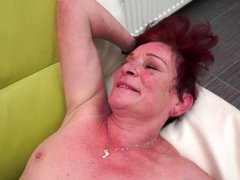 A granny with short red hair is getting penetrated in her depilated snatch