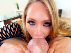 A blonde licks the balls in front of the camera lens, close up