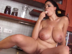 A porky kitten is in the kitchen and she is playing with her large boobs