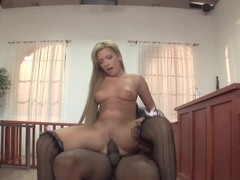 A dude with a huge black cock is fucking a hot little blonde