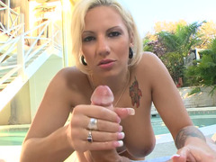 A blonde with tattoos is giving a good hand job in the pool