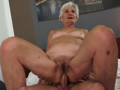 A nasty mature short haired granny is sucking a big hard pecker