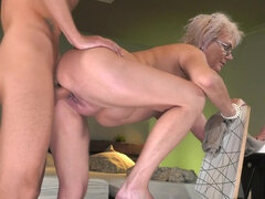 Short-haired granny with glasses gets deeply fucked and facialized