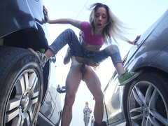 A blonde is between two cars and she is sucking a dick well