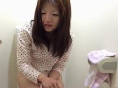Asian nerd broad is peeing in a toilet and gets spied on