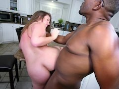 A blonde is having interracial sex in the kitchen on the counter