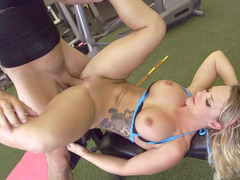 A blonde shakes her sizeable tits while she is naked in the gym