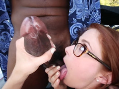 Redhead with glasses is tasting a big dark meat stick. She rides it too