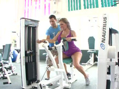 A busty woman is in the gym and she is getting her tight ass licked
